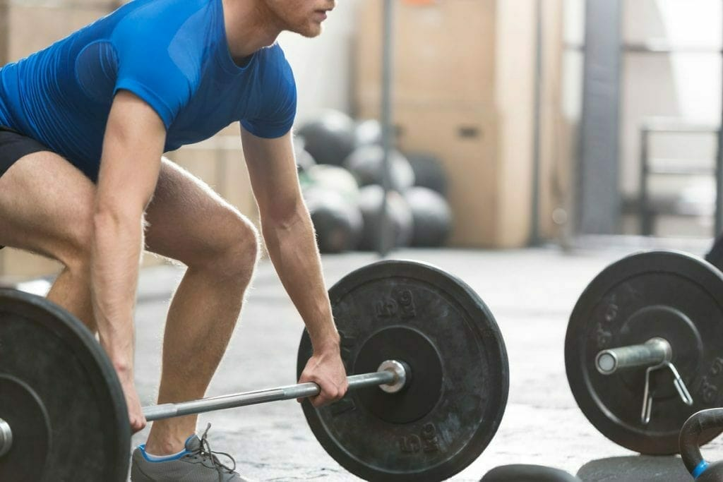 CrossFit athlete lifting barbell during WOD