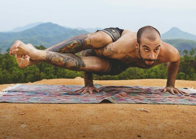 """Man doing tough """"Eka Pada Koundinyasana"""" exercise outdoors"""