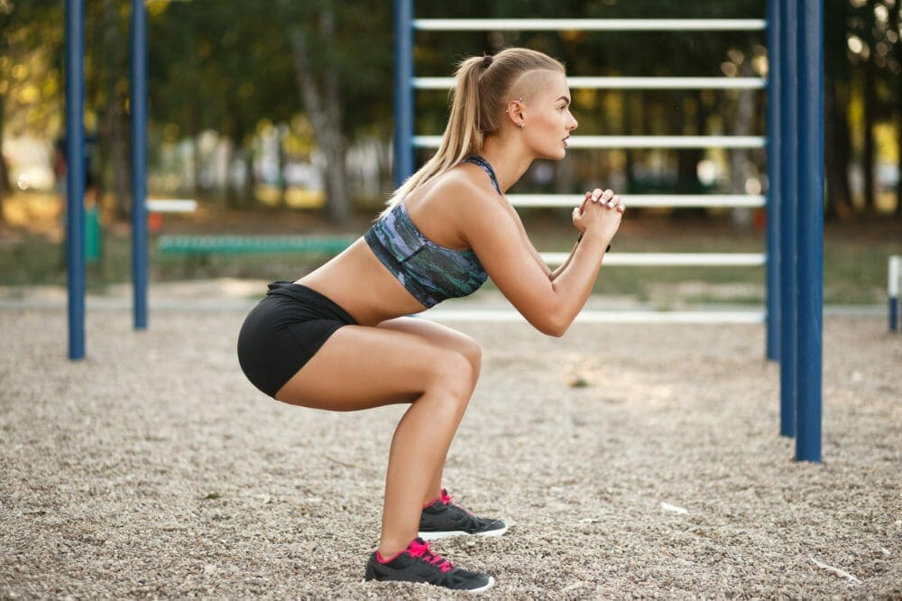 Deep squat. Side view of young beautiful woman in sportswear and piercing doing squat  while standing on the sport ground in the park.