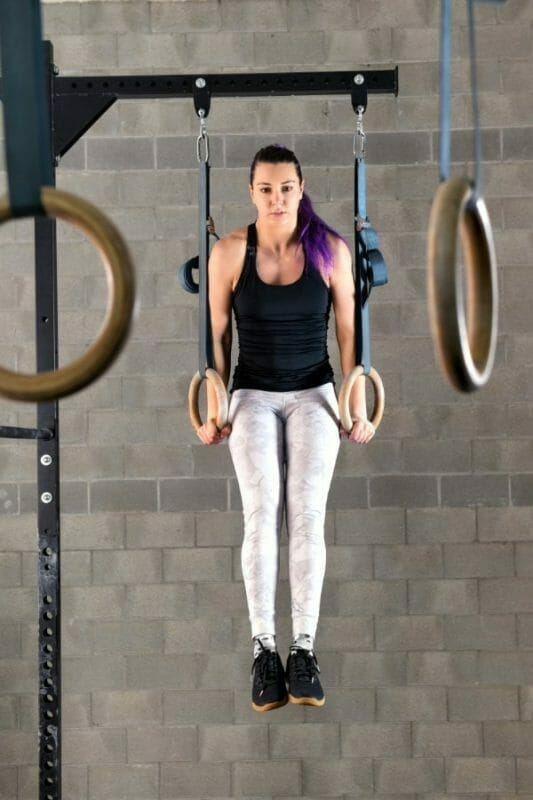 Young woman athlete doing muscle up exercises on rings during her workout in the gym in a full length frontal view raised on extended arms
