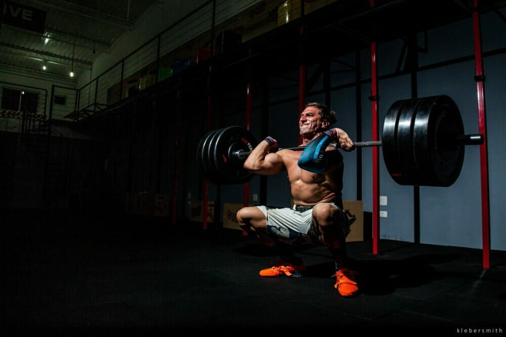man using wrist straps for power clean