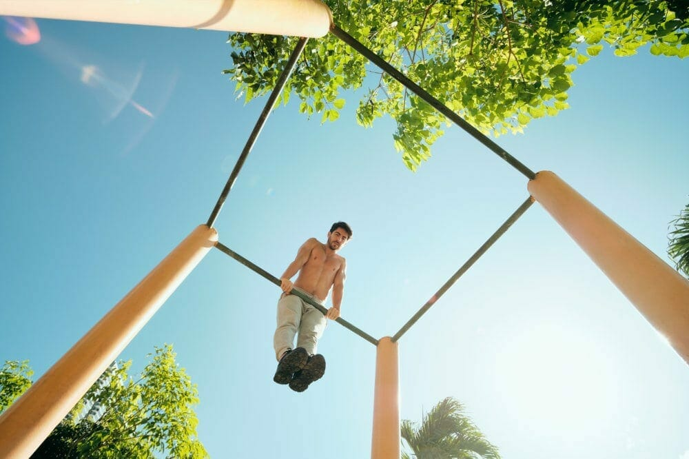 Man doing muscle-ups on outdoor bars